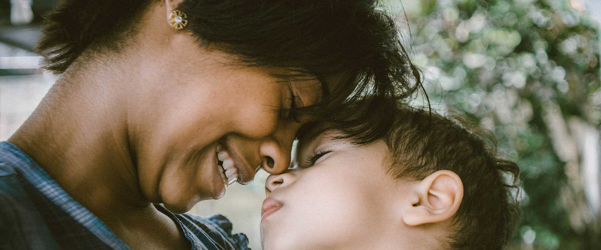 woman smiling and leaning in with her forehead rested on childs forehead