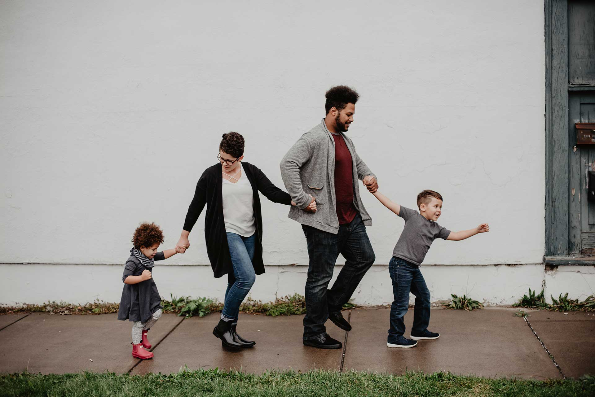 father mother and two children holding hands walking on a sidewalk