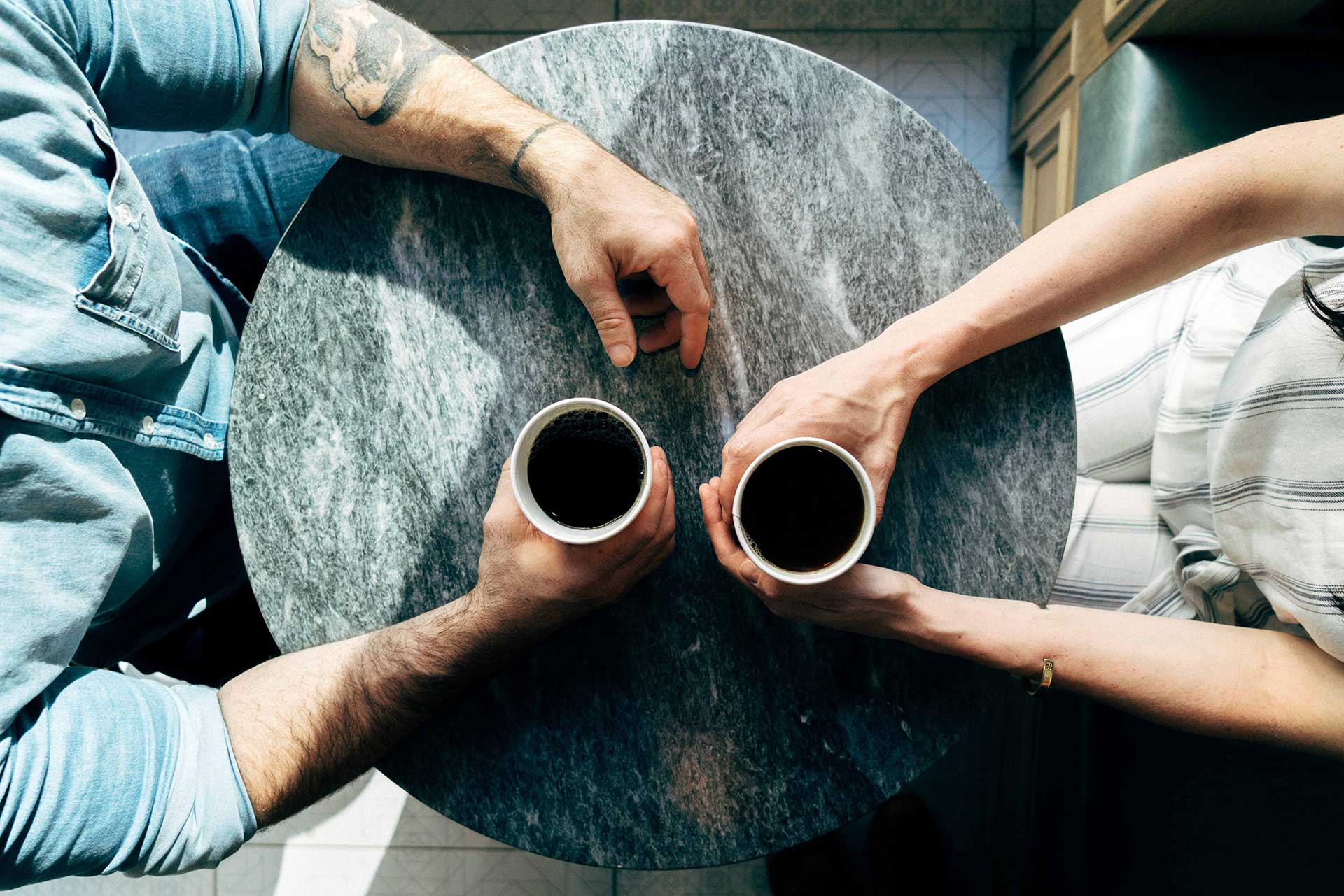 top down view of man and woman holding coffee cups on table