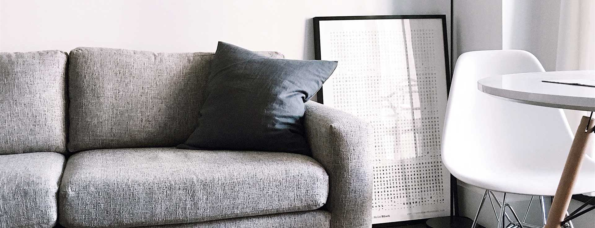 grey couch framed artwork chair and table in room