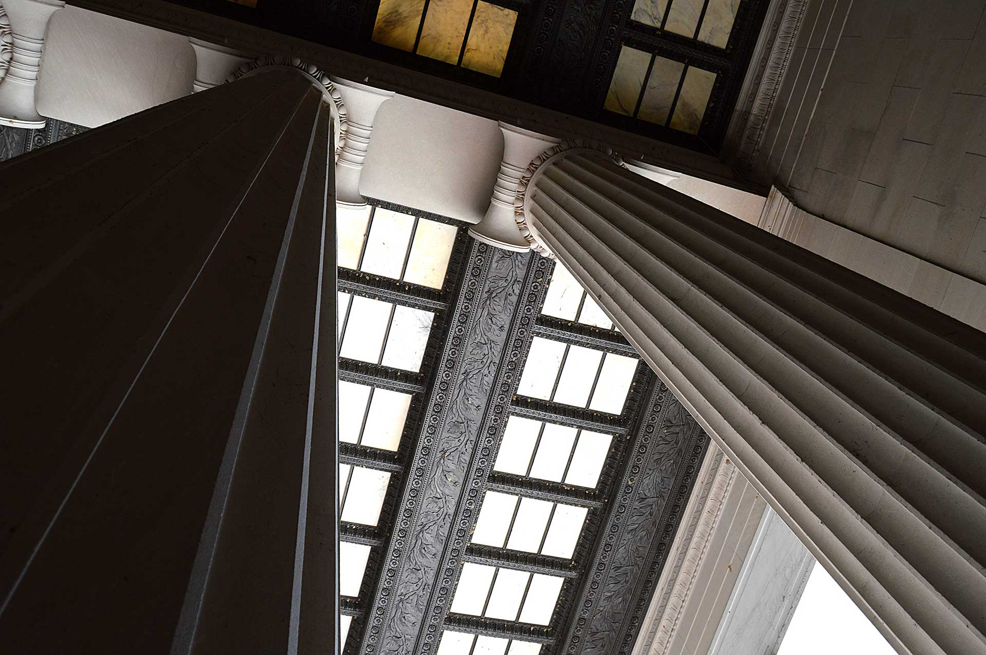 looking up towards ceiling at tall stone pillars